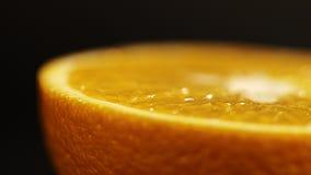 Πορτοκάλι στενό σε έναν επάνω τμημάτων Φωτεινά εσπεριδοειδή σε ένα μαύρο υπόβαθρο η πορτοκαλιά περικοπή στο μισό βρίσκεται κλείστ απόθεμα βίντεο