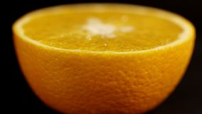 Πορτοκάλι στενό σε έναν επάνω τμημάτων Φωτεινό πορτοκάλι εσπεριδοειδών σε ένα μαύρο υπόβαθρο κλείστε επάνω Φρέσκα εσπεριδοειδή στ απόθεμα βίντεο
