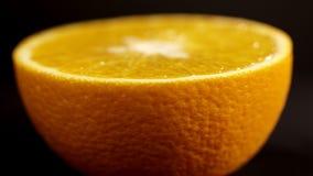 Πορτοκάλι στενό σε έναν επάνω τμημάτων Φωτεινό πορτοκάλι εσπεριδοειδών σε ένα μαύρο υπόβαθρο κλείστε επάνω Φρέσκα εσπεριδοειδή στ φιλμ μικρού μήκους