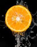 Πορτοκάλι στο νερό σε ένα μαύρο υπόβαθρο Στοκ φωτογραφίες με δικαίωμα ελεύθερης χρήσης