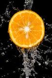 Πορτοκάλι στο νερό σε ένα μαύρο υπόβαθρο Στοκ Φωτογραφίες