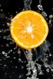 Πορτοκάλι στο νερό σε ένα μαύρο υπόβαθρο Στοκ Εικόνες