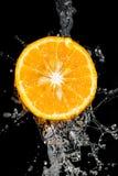 Πορτοκάλι στο νερό σε ένα μαύρο υπόβαθρο Στοκ Φωτογραφία