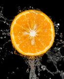 Πορτοκάλι στο νερό σε ένα μαύρο υπόβαθρο Στοκ φωτογραφία με δικαίωμα ελεύθερης χρήσης