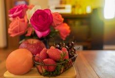 Πορτοκάλι, Apple, κεράσι & φράουλα στον πίνακα με τα τριαντάφυλλα στο α Στοκ Εικόνες