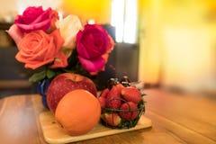 Πορτοκάλι, Apple, κεράσι & φράουλα στον πίνακα με τα τριαντάφυλλα στο α Στοκ εικόνα με δικαίωμα ελεύθερης χρήσης