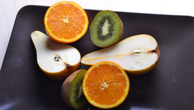 Πορτοκάλια, ακτινίδιο, αχλάδια που κόβονται σε ένα σκοτεινό χρώμα πιάτων Στοκ φωτογραφία με δικαίωμα ελεύθερης χρήσης