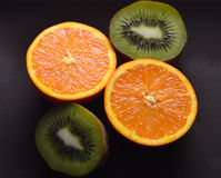 Πορτοκάλια, ακτινίδιο, περικοπή σε ένα σκοτεινό χρώμα πιάτων Στοκ φωτογραφία με δικαίωμα ελεύθερης χρήσης