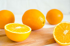 Πορτοκάλια και σε έναν ξύλινο πίνακα σε ένα άσπρο ξύλινο υπόβαθρο Στοκ εικόνες με δικαίωμα ελεύθερης χρήσης