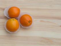 Πορτοκάλια στα μικρά καλάθια εγγράφου στην ξύλινη σύσταση Στοκ Εικόνα