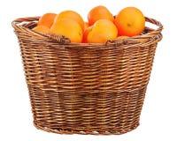 Πορτοκάλια στο ψάθινο καλάθι που απομονώνεται στο λευκό. Στοκ Εικόνα