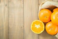 Πορτοκάλια gunny στο σάκο και τις φέτες μια στον ξύλινο πίνακα Στοκ φωτογραφίες με δικαίωμα ελεύθερης χρήσης