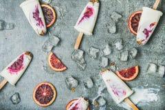 Πορτοκάλι αίματος, γιαούρτι και granola popsicles στον πάγο, γκρίζο υπόβαθρο Στοκ Εικόνες