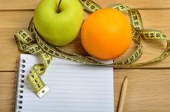 Πορτοκάλι με τα φρούτα και το σημειωματάριο μήλων Στοκ φωτογραφία με δικαίωμα ελεύθερης χρήσης