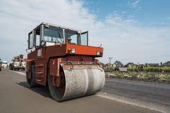 Πορτοκαλής βαρύς συμπιεστής κυλίνδρων δόνησης στις εργασίες πεζοδρομίων ασφάλτου για την οδική επισκευή Εργασία στο νέο δρόμο στοκ εικόνες