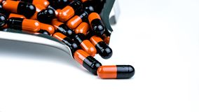 Πορτοκαλής-μαύρα χάπια καψών στο δίσκο φαρμάκων Αντίσταση φαρμάκων αντιβιοτικών Χρήση φαρμάκων με λογικό Αντιμικροβιακά χάπια καψ στοκ φωτογραφίες με δικαίωμα ελεύθερης χρήσης