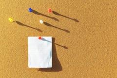 Πορτοκαλής πίνακας του Κορκ με μια σημείωση εγγράφου που καρφώνεται και διάφορες διαφορετικές καρφίτσες χρώματος ανωτέρω με τις σ στοκ φωτογραφία με δικαίωμα ελεύθερης χρήσης