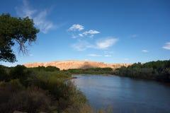 Πορτοκαλής ψαμμίτης που καίγεται ως σύνολα ήλιων πέρα από έναν ποταμό στην έρημο στοκ εικόνα με δικαίωμα ελεύθερης χρήσης