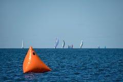 Πορτοκαλής sailboat δείκτης φυλών στη λίμνη Στοκ Εικόνα