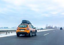 Πορτοκαλί αυτοκίνητο με το κιβώτιο αποσκευών στεγών στην εθνική οδό Έννοια οικογενειακού ταξιδιού στοκ εικόνα