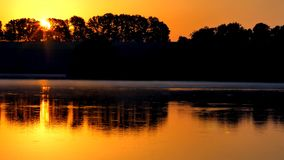 Πορτοκαλί ηλιοβασίλεμα στον ποταμό Ηλιοβασίλεμα πέρα από τη λίμνη φιλμ μικρού μήκους
