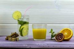 πορτοκαλί θερινό ύδωρ πάγου ποτών εσπεριδοειδών καραφών Ένα ποτήρι του χυμού από πορτοκάλι, ένα γυαλί Mojito Τεμαχισμένο πορτοκάλ Στοκ φωτογραφία με δικαίωμα ελεύθερης χρήσης