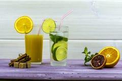 πορτοκαλί θερινό ύδωρ πάγου ποτών εσπεριδοειδών καραφών Ένα ποτήρι του χυμού από πορτοκάλι, ένα γυαλί Mojito Τεμαχισμένο πορτοκάλ Στοκ Εικόνα