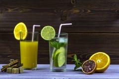 πορτοκαλί θερινό ύδωρ πάγου ποτών εσπεριδοειδών καραφών Ένα ποτήρι του χυμού από πορτοκάλι, ένα γυαλί Mojito Τεμαχισμένο πορτοκάλ Στοκ Εικόνες