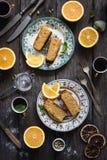 Πορτοκαλί κέικ που εξυπηρετείται στο εκλεκτής ποιότητας πιάτο στο αγροτικό ξύλινο επιτραπέζιο υπόβαθρο Στοκ Φωτογραφία