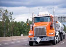 Πορτοκαλί μεγάλο τρακτέρ φορτηγών εγκαταστάσεων γεώτρησης ημι με το transpo δύο ρυμουλκών δεξαμενών Στοκ εικόνα με δικαίωμα ελεύθερης χρήσης