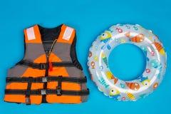 Πορτοκαλί σακάκι ζωής και διογκώσιμος κύκλος κωπηλασίας για τα παιδιά, την έννοια του καλοκαιριού και τη διάσωση ανθρωπίνων ζωών  στοκ εικόνες