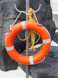 Πορτοκαλί συντηρητικό ζωνών ασφαλείας ή ζωής με το κίτρινο σχοινί συνημμένο Στοκ Φωτογραφίες
