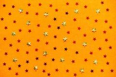 Πορτοκαλί υπόβαθρο με τα κίτρινα και κόκκινα αστέρια Εορταστική αφηρημένη έννοια στοκ εικόνες
