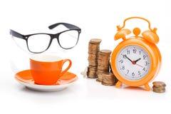 πορτοκαλί φλυτζάνι και ξυπνητήρι, νομίσματα και γυαλιά Στοκ Εικόνες