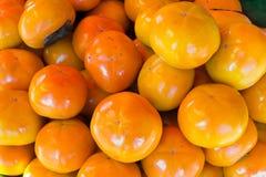 Πορτοκαλί persimmon στο πάτωμα, πορτοκαλί persimmon στο πάτωμα Στοκ Φωτογραφίες
