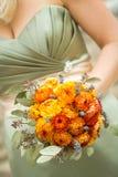 Πορτοκαλιά ανθοδέσμη που κατέχει η παράνυμφος στοκ εικόνες