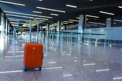 Πορτοκαλιά βαλίτσα στη αίθουσα αναμονής στον αερολιμένα Στοκ Φωτογραφία