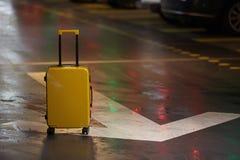 Πορτοκαλιά βαλίτσα στο δρόμο στην πόλη Θερινές διακοπές και έννοια ταξιδιού στοκ εικόνες
