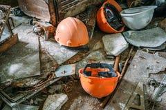 Πορτοκαλιά κράνη στο βρώμικο πάτωμα στο εγκαταλειμμένο εργοστάσιο, έννοια οικονομίας Στοκ Εικόνες