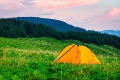 Πορτοκαλιά σκηνή στο πράσινο λιβάδι στο υπόβαθρο των βουνών στοκ φωτογραφία με δικαίωμα ελεύθερης χρήσης