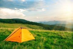 Πορτοκαλιά σκηνή τουριστών στα βουνά κάτω από το φωτεινό ήλιο στοκ εικόνες