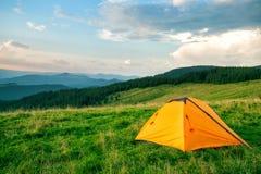 Πορτοκαλιά σκηνή τουριστών στα πράσινα βουνά στοκ εικόνα με δικαίωμα ελεύθερης χρήσης
