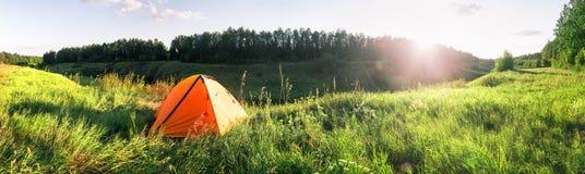 Πορτοκαλιά σκηνή τουριστών στην πράσινη χλόη κάτω από τον ήλιο ρύθμισης στοκ εικόνες