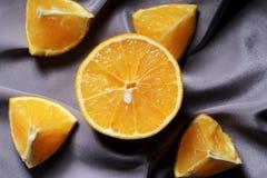 Πορτοκαλιά τμήματα σε ένα γκρίζο ύφασμα στοκ φωτογραφία με δικαίωμα ελεύθερης χρήσης