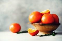 Πορτοκαλιά tangerines, μανταρίνια, κλημεντίνες, εσπεριδοειδή με το δεντρολίβανο στο ξύλινο κιβώτιο στο γκρίζο υπόβαθρο concrepe,  στοκ φωτογραφία