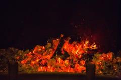 Πορτοκαλιές φλόγες στην τέφρα στην εστία στοκ εικόνες