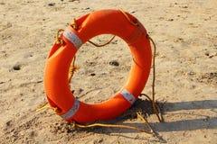 Πορτοκαλής άσπρος lifebuoy στην άμμο Στοκ Εικόνες