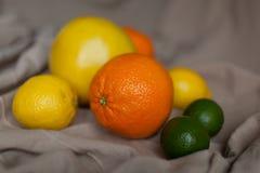 Πορτοκαλής ασβέστης λεμονιών στον πίνακα με το ύφασμα Στοκ Εικόνες