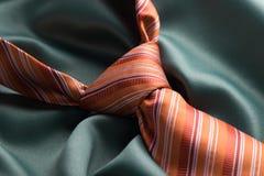 Πορτοκαλής δεσμός στο πράσινο μετάξι Στοκ Εικόνες