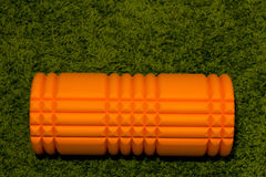 Πορτοκαλής κύλινδρος αφρού στο πράσινο υπόβαθρο στοκ εικόνες
